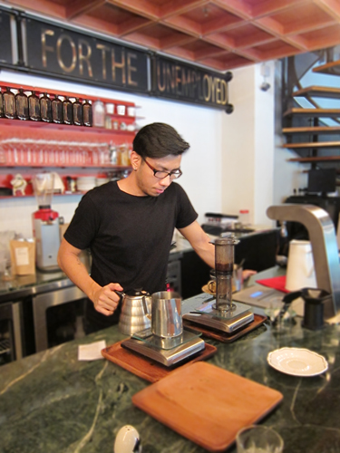 Barista using french press to make coffee
